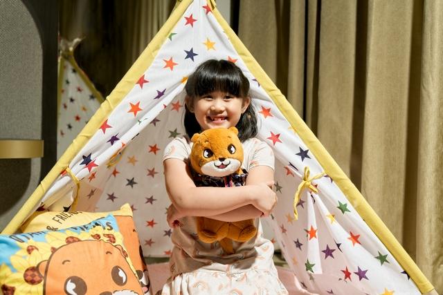 Child hugging otah soft toy in batik